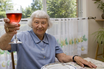 Senior woman toasting with a glass of wine