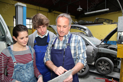 Teenagers in professional training with garage woner - 30419964