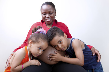 Kids listening to mom`s pregnant belly