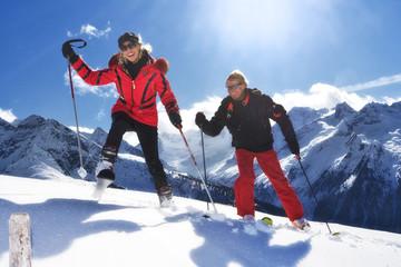 Zwei Skifahrer steigen Schneehang hoch