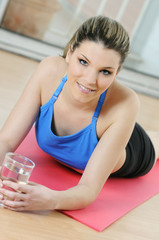 young athletic woman lying with a glass of water