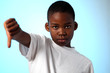 Young african boy thumbs down sign on color background