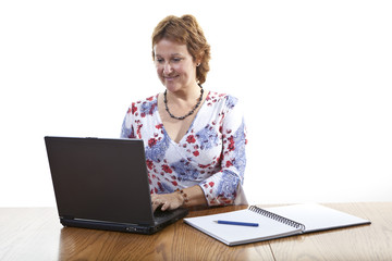 Happy smiling businesswoman working on a laptop