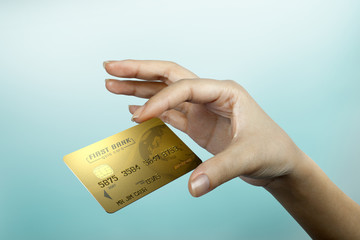 a woman hand with a gold credit card