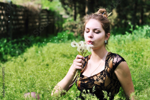 girl blowing on dandelions