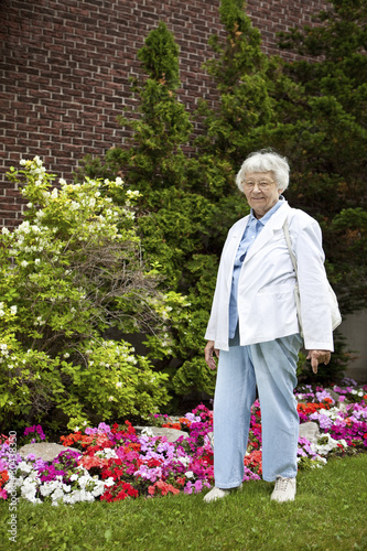 Senior woman with garden and building background