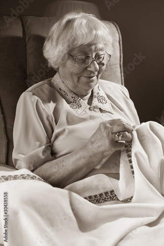 Active senior woman embroidering
