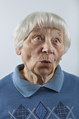 Amazed senior woman head and shoulders portrait