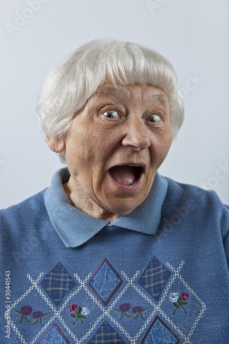 Happy surprised senior woman head and shoulders portrait