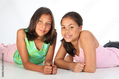 Two teenage girls relaxed lying on studio floor