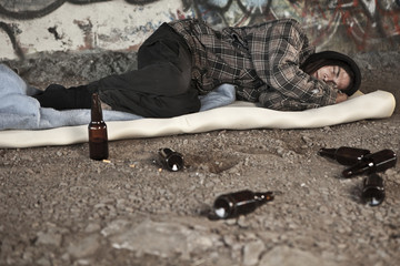 Homeless alcoholic sleeping outdoors