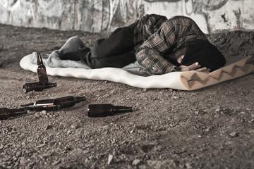 Homeless alcoholic sleeping outdoors