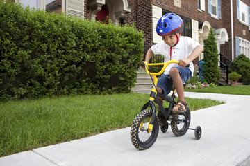 Young boy riding his first bicycle with training wheels