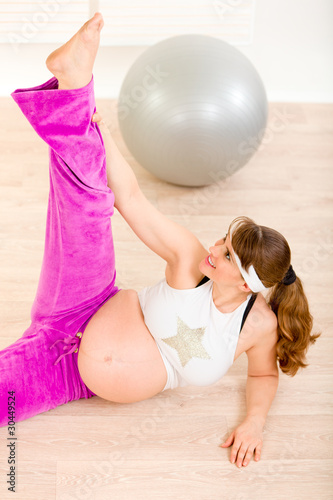 Tuinposter Gymnastiek Smiling attractive pregnant woman doing stretching exercises .