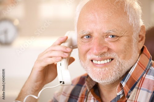 Portrait of smiling senior using landline phone - 30450591