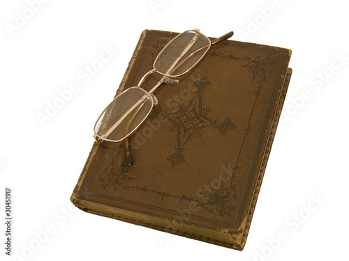 Old book with brown leather cover and gold-rimmed spectacles
