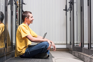 The engineer sits front equipment in datacenter