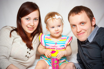 Bright picture of happy family with baby over white