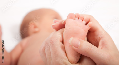 Mother's hands massaging little baby's foot