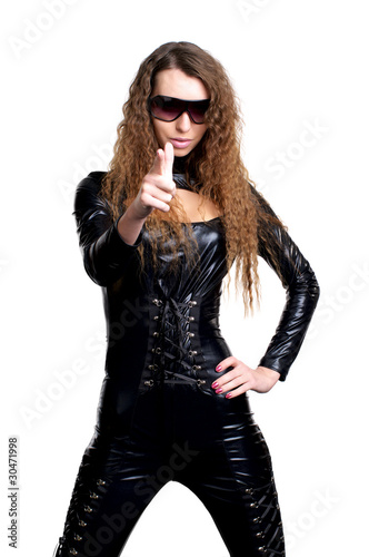Sexy woman in skintight latex pointing at you