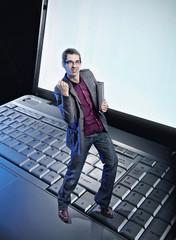 Conceptual photo of a happy man standing on the laptop's keyboar