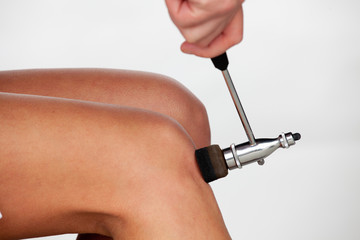 The neurologist testing knee reflex using a hammer