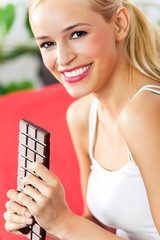 Portrait of young happy woman eating chocolate at home