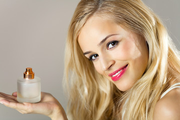 Young happy smiling woman with perfum bottle indoors