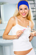 Young woman with toothbrush and glass of water at bathroom