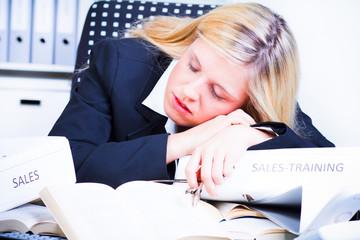 frau hängt schlafend über einen aktenberg