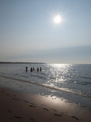 silhouettes of teenage boys playing at the beach