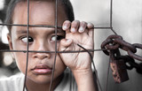 boy behind fence in Asia depicting poverty - focus on hand poster