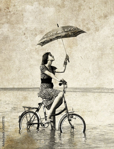 Girl with umbrella on bike. Photo in old image style. - 30497770