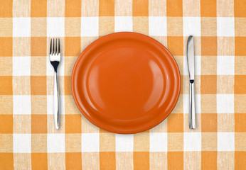Knife, orange plate and fork on yellow checked tablecloth