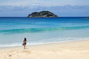 jeune femme sur plage de sable blanc aux Seychelles