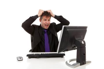 Businessman sitting behind desk is in despair, pulling his hair