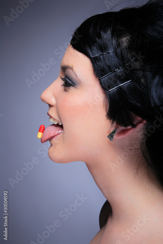 Young woman eating a pill