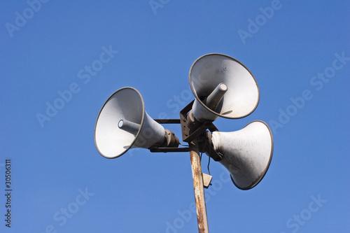 Drei Lautsprecher an einem Pfahl.
