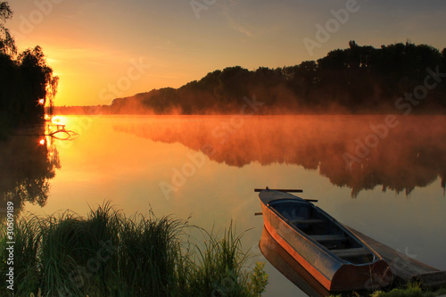 Boat on the shore of a misty lake