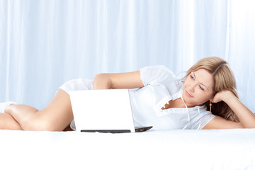 woman lying on bed with laptop