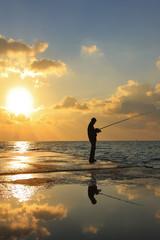 Fisherman against dawn sky