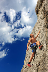 Rock climber on a rock against the blue sky