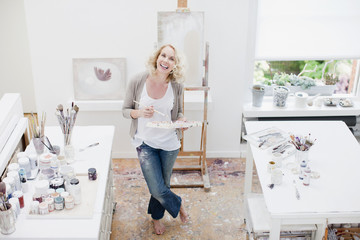 Woman holding paintbrush and palette in art studio