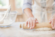 Woman rolling dough with rolling pin on kitchen counter