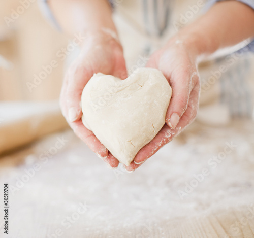 Close up of woman holding heart-shape dough