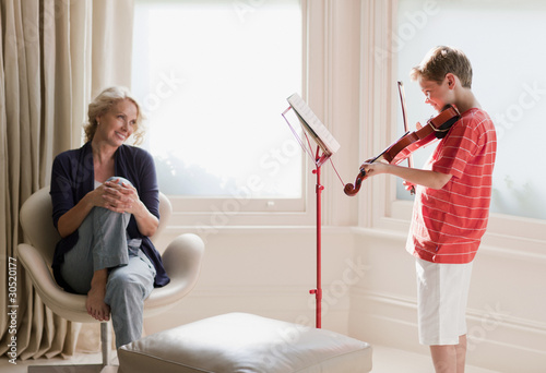 Smiling woman watching boy play violin