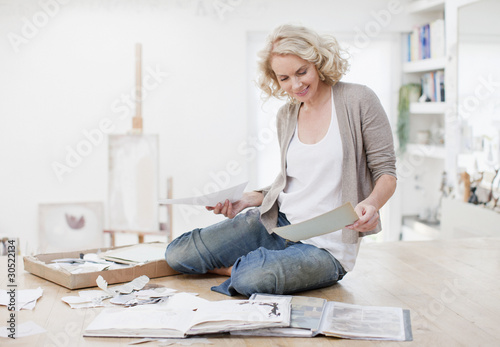 Smiling woman with photograph album and scrapbook