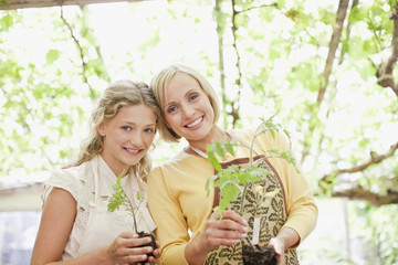 Smiling mother and daughter holding seedlings