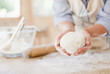 Woman holding ball of dough in kitchen