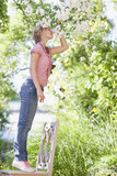 Girl standing on chair and reaching to smell flowers growing on tree